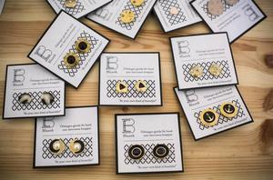 Idas örhängen som är gjorda av återvunna knappar.