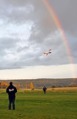 Jesper Hellström Östling styr sitt flygplan upp mot regnbågen. Ulf Höglin i bakgrunden ser ut att vara på väg att gräva guld vid regnbågens slut, men är