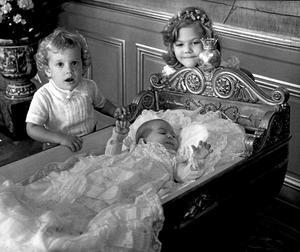 1982. Prinsessan Madeleine i dopklänning liggande i en  ornerad vagga. Victoria och Carl Philip står bredvid sin lillasyster.