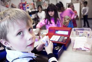 Albin Engelmark, 6 år, står i kassan och ska ge växel till Julita Gökmen som handlar i barnens mataffär.