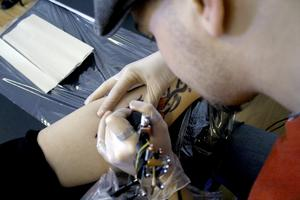 Konst med nålar. Tatueraren Fredrik Ahl färgsätter en röd blomma på Jenny Erikssons ben.