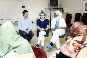 Vårdcentralchefen Vesa Juujärvi, distrikstssjuksköterskan Siv Andersson och undersköterskan och tolken Farhia Abdi samtalar med en grupp nyblivna föräldrar från Somalia.