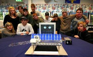 Samtliga i elever i andra årskurs på teknik- och företagarprogrammet i Timrå gymnasium plus ytterligare några som saknas på bilden har varit med att skapa den robot i förgrunden som vann designepriset i Eskilstuna.