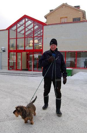 Entré. Göte Lövgren tillsammans med den strävhåriga taxen Nicko utanför Lindberghallens nya entré mot tåg- och busshållplatsen.