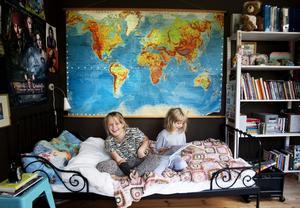 En annan värld. På väggen i Livs rum hänger en karta från en svunnen tid. Malva däremot drömmer sig gärna bort till sitt eget fantasiland Maldiverna på Jupiter.