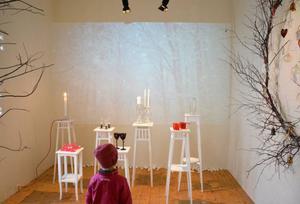 På Storsjöhyttans  julutställning fladdrar snöflingor som fond i ett skogslandskap