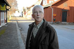 Ulf Hildebrandt framför de röda husen kring tingshusen. En av föreningens idéer är att kalla det området för Kyrkbyn.