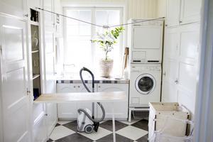 Tvättstuga med väggfasta skåp och utfällbar strykbräda kvar.