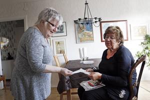Brigitta Lusth och Barbro Berger går igenom gamla bilder, inbjudningar och program från fester de haft.