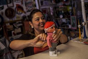 Lucia Corcuera skruvar upp en mekanisk John Blund-docka på designbutiken VEB Orange.   Foto: Johan Öberg