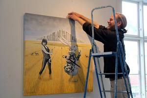 Daniel Zerbst hänger en av sina tavlor, Yes we camp XI, i utställningen hos Kulturkossan på Stenegård i Järvsö.
