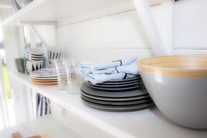 Porslin i blå, vita och grå toner i köket.