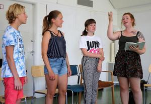 Efraim Melander Wiksten, Stina Mårtensdotter och Elsa Olsson sjunger tillsammans med sångledare Ronja Grafström.