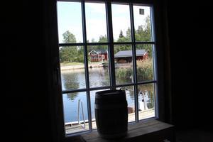 Spröjsade fönster med havsutsikt och tunga saltkar innanför.