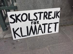 Greta Thunberg numera mycket välkända demonstrationsskylt stod lutad mot en mur medan hon intervjuades av flera journalister under fredagen.
