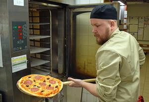 Efter tre minuter i 300 grader, plockar Björn Olli ut pizzan.