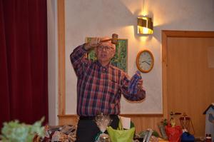 Auktionisten Olle Häggström erbjuder ett par hemstickade sockar till den köpsugna publiken. Foto: Bertil Westin