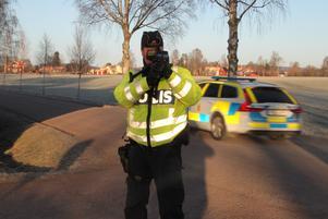 Yrkestrafikgruppens inspektör, Jocke Emanuelsson, tar sikte med lasern medan en polisbil jagar ifatt en av fredagens fortkörare.