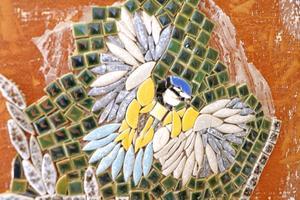 - Jag fäster mosaiken med lim och sedan fogar jag, säger Lisa och visar på den här nysatta blåmesen.