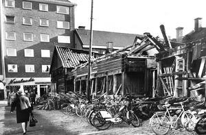 18 april 1963. Det gamla timmerhuset i hörnet Torggatan/Hantverkargatan, som innehållit både affär och vedbodar, stod först i tur att falla för rivningsmannarnas bändjärn.