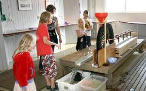 Barnen kollar in vattenhjulet i experimentverkstaden.