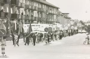 Röda fanor. Omtanke i stället för egoism ville socialdemokraterna i Surahammar ha enligt demonstrationstågets plakat 1992.