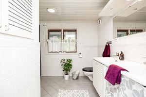 Badrummet på entréplanet har klinkergolv, golvvärme, dubbla handfat och vägghängd toalett. Foto: Länsförsäkringar Fastighetsförmedling.