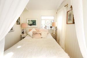 Med vit färg och en enorm passion för inredning, har Iréne Wiberg lyckats förvandla den före detta huvudentrén till ett drömskt sovrum som skymtar bakom skira, vita gardiner.