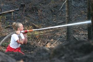 Ida Selander slet i värmen från såväl branden som solljuset under släckningsarbetet av skogsbranden nära Hålsjön i Haninge kommun i onsdags.Foto: Solveig S Thörnblom