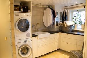 Tvättstugan har köksinredning från Ikea. Klädstången är egentligen en guldfärgad gardinstång.