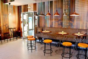 I kaféet finns många lampor med mjuk belysning och höga barmöbler i koppartoner och orange.