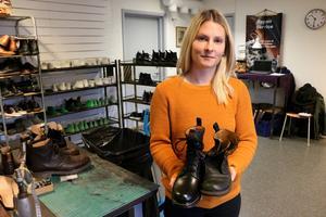 Pia Karlsson på Kavat håller upp ett par gamla kängor som nu säljs i