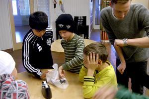 Samarbete. Tillsammans ska Muhammet Dihad och Max Lundholm slå in ett paket, med en hand på ryggen. Fritidsledaren Martin Modig tar tid medan William Lindin Bäcklund och Rasmus Janetzky ser på.
