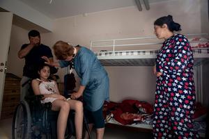 I sängen bakom ligger Leyla, som inte vaknar. Dilan, i rullstol, håller på att somna in i samma dvala.