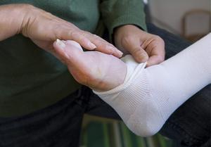 En fot blir omlagd av en distriktssjuksköterska.  Foto Claudio Bresciani