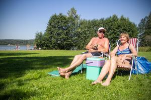 Avestaparet Rolf och Ann-Charlotte Åman kopplar av med en varsin smörgås på torra land, innan mer sol och bad väntar på campingbadet.