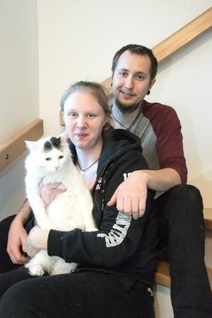 Josephine Hellberg och Max Lestander med katten Kimmy som inte riktigt vill samarbeta med fotografen.