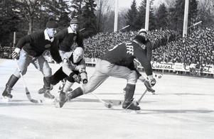 Kurt Sedvall vräker sig fram mellan tre Skutskärsspelare under omspelet på studenternas 1964.