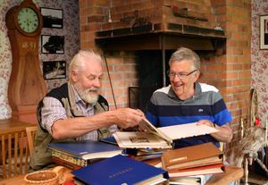 Torleif Lundh och Börje Bergqvist tittar genom pärmarna och skrattar åt Torleifs minnen av fadern Gustavs skämtlynne.