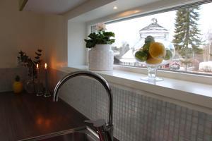 Mosaik och långsmalt fönster över bänken.