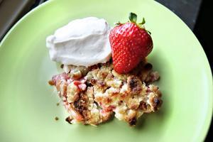 Jordgubbar och rabarber i förening. En god och knäckig paj serveras med en klick grädde.