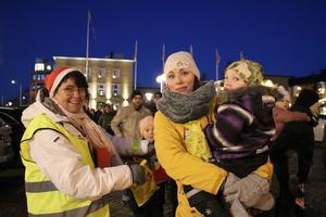 Eva från Lions delade ut godispåsar till alla barnen när de hade avslutat julgransplundringen med en långdans runt torget och förbi affärerna. Ivar Sverkersson och Sandra Ramstedt tog emot en påse.