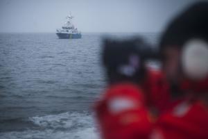 Med hjälp av kikare letar sjöräddarna efter tecken på var båten med fiskarna kan ha försvunnit.