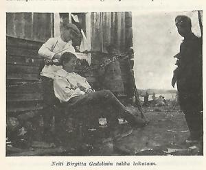 I Nystadskårens historik hittar vi flickan i byxorna. Det var den då 22-åriga fröken Birgitta Gadolin (1895-1982). Hennes titel i matrikeln är gymnastiklärare och hon hade funktionen sanitär (fältsjukvårdare) under tiden efter Åland. Hon deltog under hela kårens kampanj.Här är en bild från historiken utgiven 1928, där fröken Birgitta Gadolin låter klippa sitt hår. Senare i livet kom hon att översätta reseböcker och ge ut tre memoarböcker.