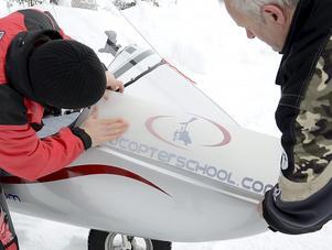 Jens Wemmel och Mikael Vuorijärvi i föreningen Ultraflyers Bergslagen fäster en dekal som slår ett slag för utbildningen till pilot i ultralätt.