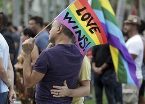 Kärleken vinner, står det på regnbågsflaggan som ett homosexuellt par håller upp på en av de många manifestationerna i USA för att hedra offren för det värsta massmordet i landets moderna historia.