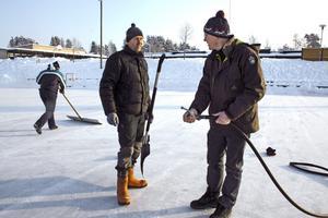 Kalle Eriksson, till vänster, och Sven Lannhard försöker värma upp vattnet i vattenslagen som denna kalla morgon har frusit.