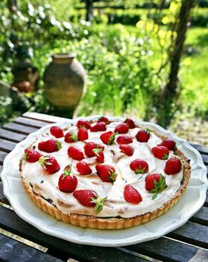 Rabarberpajen kryddas med kardemumma och toppas med marängsmet och jordgubbar.