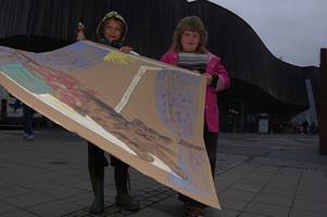 Konst utanför museet. Utanför museét höll barn på med Pröysenmotiv. Här ses Trude och Christoffer med en teckning utanför museet som i folkmun kallas för flygeln.