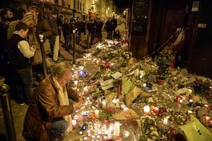 Människor lägger ner blommor vid en minnesplats vid restaurangerna på Rue Alibert i Paris på söndagskvällen.